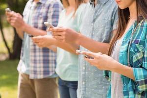 amici felici nel parco che usano i loro telefoni foto