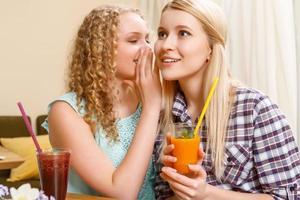 ragazza che racconta i segreti alla sua amica nella caffetteria