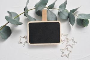 mock up di ramo di eucalipto, decorazioni di stelle e tavola di legno