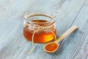 miele in un cucchiaio e un barattolo di legno foto