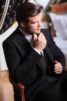 giovane uomo d'affari si siede sulla sedia vintage foto