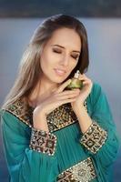 giovane donna che tiene la bottiglia di profumo nel paesaggio balneare foto