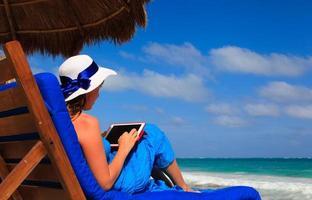 donna con touch pad sulla spiaggia tropicale