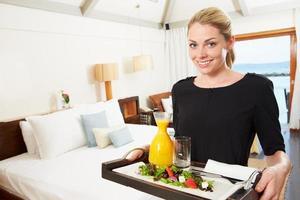 ritratto del lavoratore dell'hotel che consegna il pasto del servizio in camera foto
