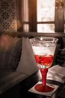 bicchiere d'acqua rosso sul tavolo con la luce del sole foto