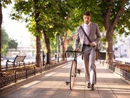uomo d'affari pensieroso che cammina con la bicicletta foto