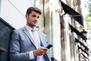uomo d'affari che tiene smartphone all'aperto foto