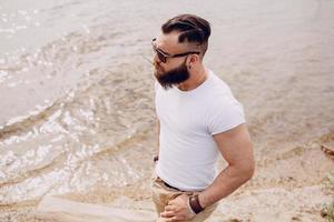 uomo barbuto sulla spiaggia foto