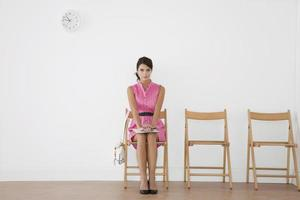 giovane donna seduta in sala d'attesa foto