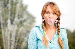 giovane studentessa dai capelli rossi in trecce codino soffia gomma da masticare foto