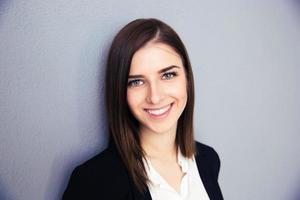 sorridente imprenditrice su sfondo grigio foto