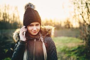 giovane donna che chiama con il telefono cellulare all'aperto in inverno foto