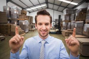 sorridente responsabile del magazzino rivolto verso l'alto con il dito foto