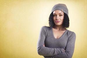 ragazza alla moda con le braccia conserte isolato su sfondo giallo. foto