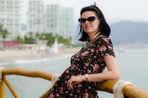 la giovane donna attraente gode del sole dalla località di soggiorno dell'oceano foto
