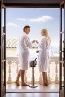 coppia in accappatoi bevendo champagne sul balcone