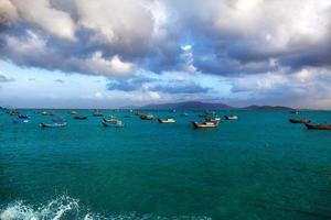 barche da pesca sul mare, uno sfondo di montagne foto