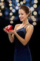donna sorridente che tiene confezione regalo rossa foto