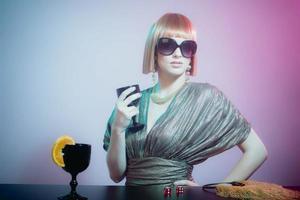donna in occhiali da sole al bar tenendo il bicchiere di vino
