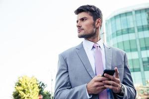 uomo d'affari utilizzando smartphone ourdoors foto