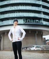 giovane donna sportiva prendendo una pausa dopo l'allenamento all'aperto foto