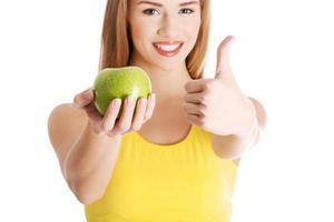 bella donna caucasica casuale che tiene mela verde fresca. foto