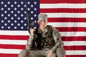 uomo dell'esercito seduto davanti a una bandiera americana foto