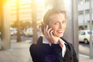 donna sorridente di affari che parla sul telefono cellulare foto