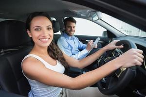 giovane donna che ottiene una lezione di guida foto