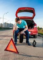 uomo seduto sulla ruota di scorta vicino a un'auto rotta