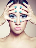 bella giovane donna con trucco luminoso e manicure foto