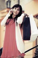 donna di modo con le borse della spesa che chiamano sul telefono cellulare