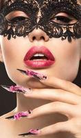 bella ragazza in maschera con unghie lunghe e labbra sensuali