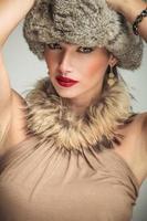volto di una bella donna con collo di pelliccia e cappello foto
