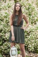 donna in abito verde alla moda in posa nel giardino estivo.
