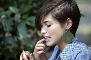 donna che applica lucidalabbra foto