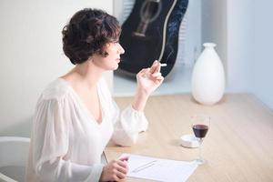 donna attraente che scrive una lettera e il fumo foto