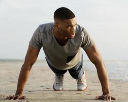 giovane atletico che fa push up in spiaggia