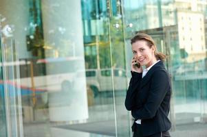 donna d'affari felice camminare e chiamare dal telefono cellulare foto