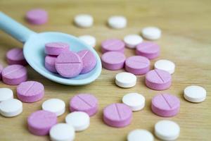 gruppo di farmaci su un cucchiaio e una tavola di legno foto