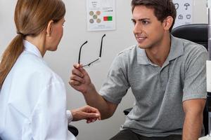medico che mostra gli occhiali foto