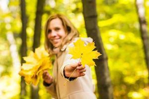 giovane donna con foglie d'autunno foto
