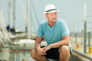 moda ritratto di bell'uomo sul molo contro gli yacht