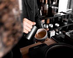 barista versando la crema in tazza foto