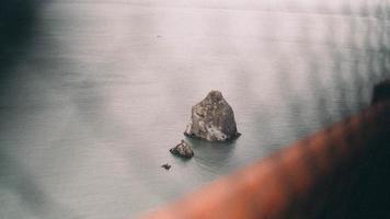formazione rocciosa sull'acqua attraverso la recinzione foto
