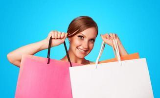 ragazza bruna con borse della spesa su backgorund blu. foto