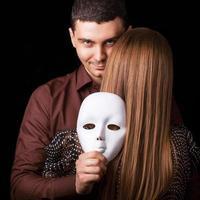 uomo di moda che tiene una faccia di maschera bianca. concetto psicologico.