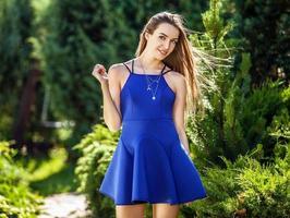 donna in abito blu alla moda in posa nel giardino estivo.