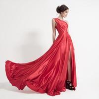 giovane donna di bellezza in svolazzante abito rosso. sfondo bianco.