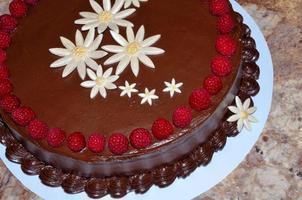 torta al cioccolato decorata con lamponi freschi e fiori fondenti foto